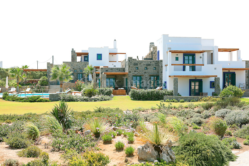 facade of luxury villa with lush yard..In 2001, architect Panagis Kyrtsis built a complex of two residential properties on the island of Paros, Greece. Both houses incorporate the traditional architectural elements of the island with the archaic abstract geometric elements of the Cycladic civilization.