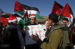An Israeli soldier confronts Palestinian protesters wearing Father Christmas outfits during a demonstration at the Howara checkpoint near Nablus, West Bank, 01 January 2015. The checkpoint is one of four main checkpoints around Nablus but despite claims by the Israeli Government that the checkpoint would be removed to allow free movement between Nablus and Ramallah to date it remains in place. Photo by Nedal Eshtayah