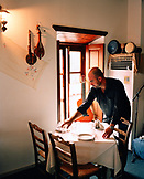GREECE, Patmos, Skala, Dodecanese Island, Yannis Kaneli sets tables for dinner at his restaurant, Taverna Tzivaeri