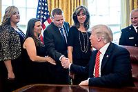 United States President Donald Trump, right, shakes hands with Darren Ellisor, a Southwest Airlines Co. first officer, next to Tammie Jo Shults, a Southwest Airlines captain, center, while meeting with the crew and passengers of Southwest Airlines flight 1380 in the Oval Office of the White House in Washington, D.C., U.S., on Tuesday, May 1, 2018. An engine on Southwest's flight 1380, a Boeing Co. 737-700 bound for Dallas from New York's LaGuardia airport, exploded and made an emergency landing on April 17 sending shrapnel into the plane and killing a passenger seated near a window. <br /> Credit: Andrew Harrer / Pool via CNP /MediaPunch