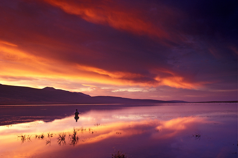 Fly fisherman on Mann Lake with sunrise. Oregon.