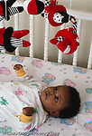 2 month old baby girl closeup, on back, in crib, watching mobile