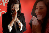 Yingluck Shinawatra, sister of ousted premier Thaksin Shinawatra greets reporters and supporters gathered at her party's headquarters after voting in general elections ended in Bangkok July 3, 2011. The opposition won Thailand's general election by a landslide on Sunday, exit polls showed, paving the way for Yingluck Shinawatra to become the country's first female prime minister in a victory for a red-shirted political movement. REUTERS/Damir Sagolj  REUTERS/Damir Sagolj (THAILAND)