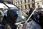 In the middle of the kettle formed by the Metropolitan Police during the second student protest, masked demonstrators use pieces of wood taken from placards to smash the windscreen of an empty stranded police van. 24/11/2010