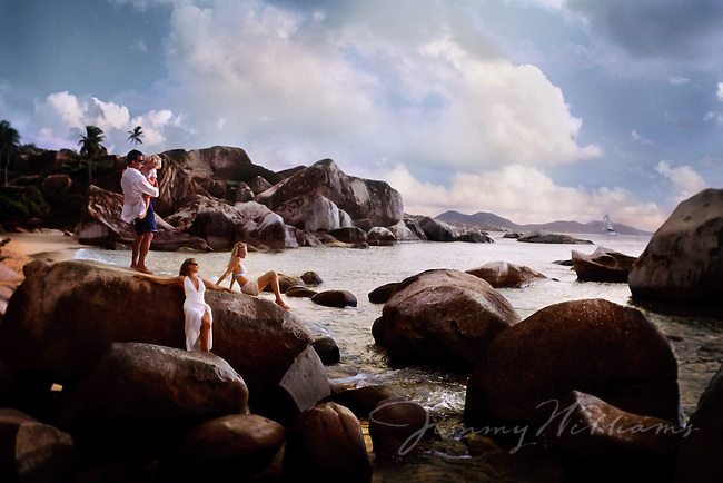 A family bonds on large rocks that scatter the shore of the British Virgin Islands