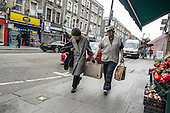 An elderly couple with shopping bags, Kilburn, London.