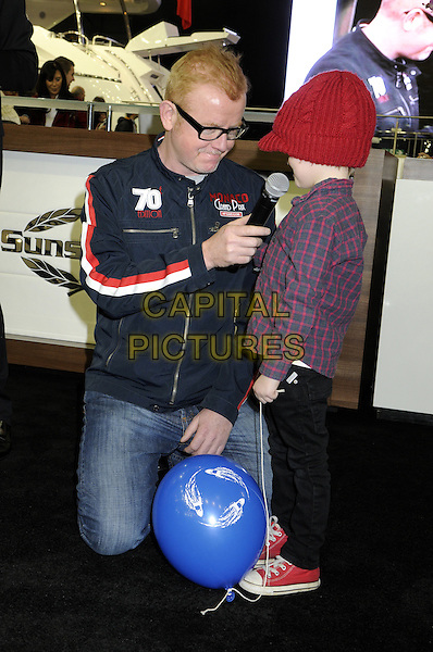 Chris Evans .At the Tullett Prebon London Boat Show Opening Day at the Excel Centre, London, England..January 12th 2012.full length black jacket jeans denim glasses white red stripe kneeling kid child microphone interview .CAP/BK/PP.©Bob Kent/PP/Capital Pictures.