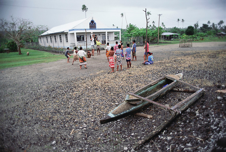 Teenagers in Poutasi village, Western Samoa, play volleyball in front of the village church. Material World Project.