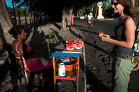 Young woman buying watermelon from street vendor, Granada, Nicaragua