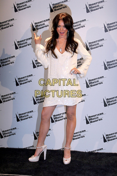 LINDSAY LOHAN.33rd Annual American Music Awards - Press Room held at the Shrine Auditorium. Los Angeles, California..USA, United States..22nd November 2005 .Ref:ADM/ZL.full length white v-neck woolen jumper dress high heels stilettoes bull rock horns hand gesture long dark hair extensions.www.capitalpictures.com.sales@capitalpictures.com.© Capital Pictures.