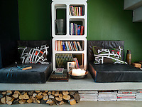 A built-in reading area under the stairs is furnished with leather-covered loungers while the raised concrete shelf on which they sit provides storage for magazines and logs