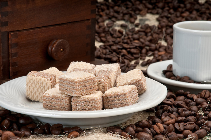 Close up of wafer cookies and coffee beans with grinder and cup.