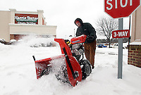 Jordon May with Williams Lawncare and Landscaping uses a snow blower to clear sidewalks in the Barracks Road Shopping Center Thursday after a snowfall in Charlottesville, VA. Photo/Andrew Shurtleff