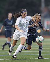 Boston Aztec defender Chelsea Roche (15) on the attack as Seacoast United Phantoms player Rachel Hill (6) defends.  In a Women's Premier Soccer League (WPSL) match, Boston Aztec (white) defeated Seacoast United Phantoms (blue), 3-0, at North Reading High School Stadium on Arthur J. Kenney Athletic Field on on June 25, 2013.