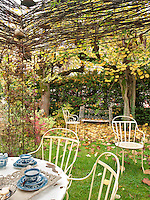 A metal table and chairs are set out on the lawn of a secluded garden.