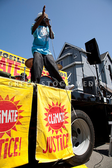 August 15, 2009. Rap artist Virtuous performs on stage. About two hundred people participated in a rally, march, and demonstration protesting Chevron's Richmond oil refinery renovation and expansion project. The event was organized by Mobilization for Climate Justice-West, a coalition of over thirty organizations, working to bring awareness to the refinery issue as well as the United Nations Climate Change Conference taking place in December in Copenhagen. Event organizers claim that the Richmond refinery project will allow the facility to refine heavier and dirtier crude that will result in more air pollution, greenhouse gas (GHGs) emissions, and health risks. A court ruling recently put the refinery project on hold saying that further environmental impact reporting was needed. Many protesters were also concerned about the environmental and human health impacts of oil company projects outside the United States. Richmond, California, USA