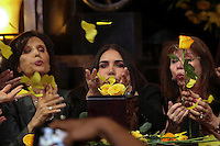 Mexico City, Mexico. 21th April 2014 - Women blows yellow flowers while they attend the funeral service of Colombian Nobel Prize laureate Gabriel Garcia Marquez in Mexico City. Photo by Miguel Pantaleon/VIEWpress