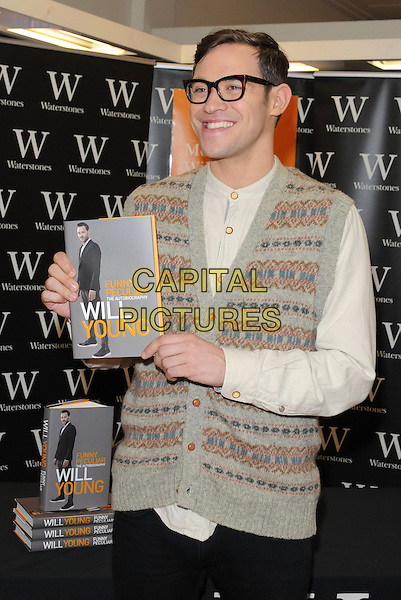 "Will Young .signs Copies Of His New Book ""Funny Peculiar"" At Waterstones, Bluewater Shopping Centre, Greenhithe, Kent, UK, 19th October 2012..half length glasses sleeveless sweater vest cardigan waistcoat knitted geek shirt collarless white cream grey gray patterned holding book .CAP/BRC.©Ben Rector/Capital Pictures."