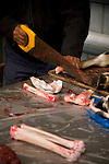 A man saws through the bone of a reindeer at the game market in Nuuk, Greenland.