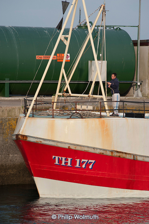 A man ties up his fishing boat in Padstow Harbour, Cornwall.