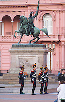 The Casa Rosada, pink house, or Casa Gobierno, housing the government on Plaza de Mayo May square. Changing of the honour guard military soldiers in parade uniform in front of an equestrian horse statue Buenos Aires Argentina, South America