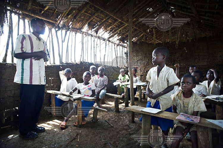 A teacher holds a class in a school made from mud and sticks.