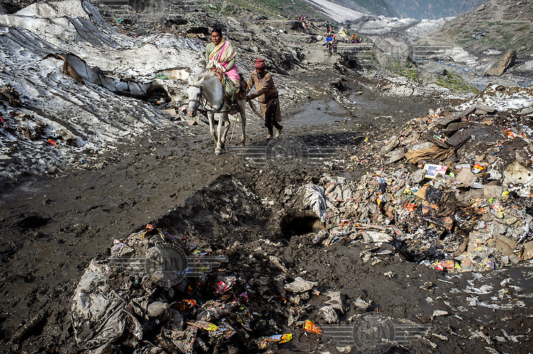 A pile of garbage seen strewn on the glaciers while a guide pushes his pony along the Amarnath trekking route in Kashmir. Hindu pilgrims brave sub zero temperatures and high altitude passes and make their pilgrimage to reach the sacred Amarnath cave, which houses a lingam - a stylized phallus, worshipped by Hindus as a symbol of God Shiva.