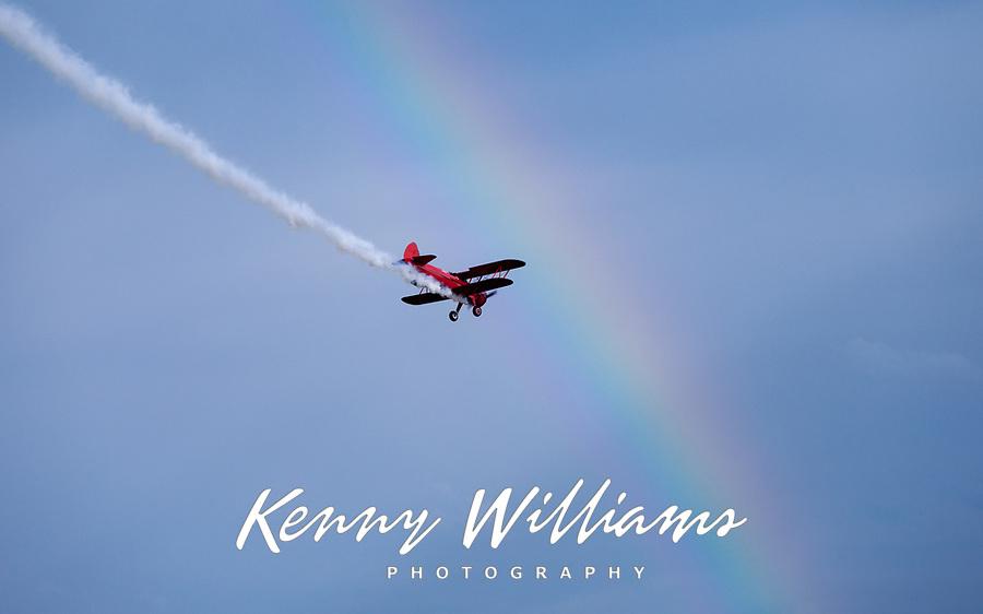 Red vintage biplane flying through rainbow, Arlington Fly-In 2016, Washington State, USA.