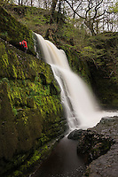 Person stands near Sgwd Clun-Gwyn Waterfall - Afon Mellte river, near Ystradfellte, Brecon Beacons national park, Wales