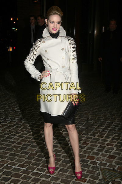 "JULIE ORDON.The Special Screening of ""Cracks"" held at the Tribeca Grand Hotel, New York, NY, USA..March 16th, 2011.full length white mac jacket gold studs studded red pink peep toe shoes clutch bag dress hand on hip.CAP/LNC/TOM.©TOM/LNC/Capital Pictures."