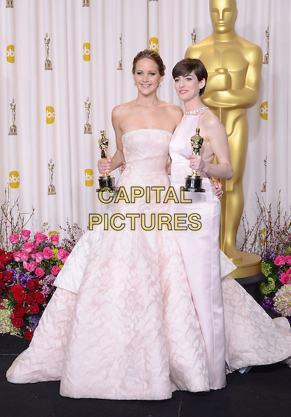 Jennifer Lawrence, Anne Hathaway.85th Annual Academy Awards held at the Dolby Theatre at Hollywood & Highland Center, Hollywood, California, USA..February 24th, 2013.pressroom oscars full length white award trophy trophies winner winners white pink pale strapless dress trophies winners .CAP/ADM.CAP/ADM/RE.©Russ Elliot/AdMedia/Capital Pictures.