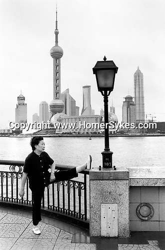 China, Shanghai. Morning exercises on the Bund.  The distinctive balconettes overlooking the Huangpu are part of the new Bund embankment which was completed between 1991 and 1993.  The Bund was enlarged by reclaiming land from the river, a process that began in the 1960s, and was later embanked.  All the buildings visible in Pudong across the river have been completed since 1993.  ..