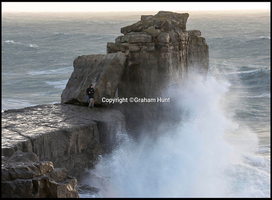 BNPS.co.uk (01202 558833)<br /> Pic: GrahamHunt/BNPS<br /> <br /> ****Please use full byline****<br /> <br /> This is the shocking moment a reckless father and a young child scaled a dangerous rock plinth as enormous waves crashed around them.<br /> <br /> The pair are thought to have gone for a walk during extreme storms and wandered 50ft from the main coastal path in Portland, Dorset.<br /> <br /> When they reached the Pulpit Rock - a huge stack of stones just off the Jurassic coast - they precariously leaned against it as massive waves splashed against the side.<br /> <br /> The man, thought to be in his 40s, was spotted desperately holding onto the child, who is believed to be his son and no older than 11.<br /> <br /> A passer-by stopped and photographed the scene in horror as the duo were soaked by the huge splashes that crashed over the rocks.