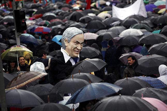 SCH05. SANTIAGO DE CHILE (CHILE), 18/08/2011.- Un muñeco del presidente de Chile, Sebastián Piñera, es visto entre miles de personas que marchan bajo la lluvia hoy, jueves 18 de agosto de 2011, en el marco de las demandas estudiantiles por una mejor educación, en Santiago (Chile). Piñera reiteró que sólo el diálogo puede conducir a una solución del conflicto. EFE/FELIPE TRUEBA