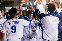 AFL West left fielder Cavan Biggio (26), of the Surprise Saguaros and Toronto Blue Jays organization, is congratulated by catcher Meibrys Viloria (9) and outfielder Buddy Reed (85) in the dugout after scoring a run during the Arizona Fall League Fall Stars game at Surprise Stadium on November 3, 2018 in Surprise, Arizona. The AFL West defeated the AFL East 7-6 . (Zachary Lucy/Four Seam Images)