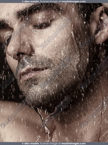 Sensual closeup portrait of a man face with closed eyes under pouring rain or shower water