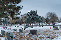 A winter scene at a small town cemetery where headstone stretch into a snowy distance under overcast skies.