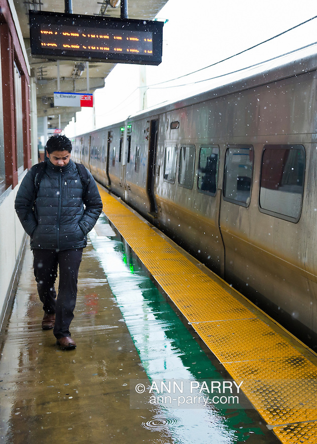 March 8, 2013 - Merrick, New York, U.S. -  Though the Long Island Railroad schedule remains good despite Nor'Easter slushy snowfall Friday afternoon on South Shore of Long Island, the cold wet winds reach even the passengers waiting under the protective overhang over platform of the elevated Merrick Train Station.