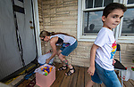 WATERBURY , CT-080720JS10—Heather Britton, a member of the Waterbury Sister Wine Fairies, along with help from her son Isaiah Hernandez, 8, delivers homemade gift baskets to a Waterbury resident on North Walnut Street on Friday. <br /> Jim Shannon Republican-American