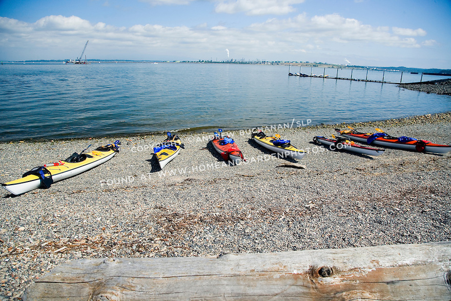 Red and yellow kayaks are lined up along the shore, awaiting a day of kayaking on the Salish Sea in the state of Washington.