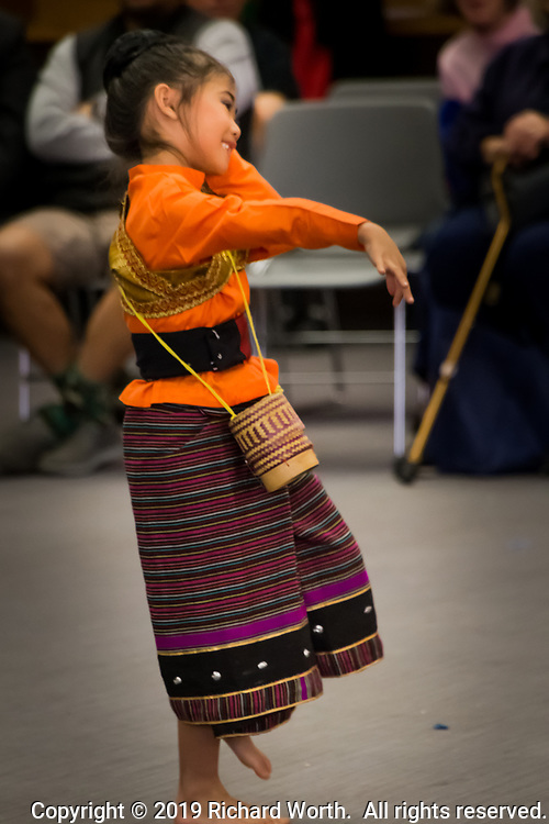 One of the young dancers from the Thai Cultural Council of Berkeley, smiling while performing at the San Leandro Library's Lunar New Year Celebration.