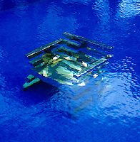 Detail of a brass chair designed by Nicholas Alvis Vega submerged in the swimming pool