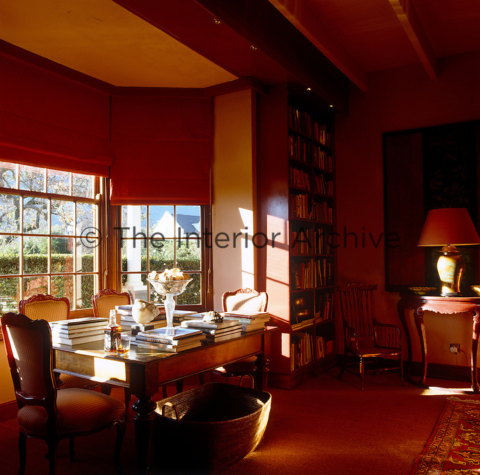 The reading table in the study has been placed in the bay window overlooking the veranda