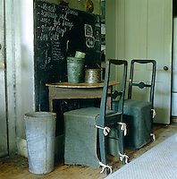 In the entrance hall two 19th century Swedish chairs are covered in rough grey linen