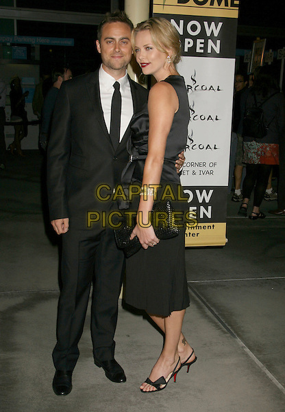 "STUART TOWNSEND & CHARLIZE THERON.""In The Valley Of Elah"" Premiere held at The Arclight Cinemas, Hollywood, California, USA..September 13th, 2007.full length black skirt satin sleeveless top suit clutch purse couple .CAP/ADM/RE.©Russ Elliot/AdMedia/Capital Pictures."