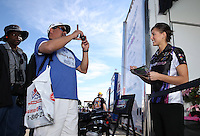 Feb. 15, 2013; Pomona, CA, USA; NHRA top fuel dragster driver Leah Pruett signs autographs during qualifying for the Winternationals at Auto Club Raceway at Pomona. Mandatory Credit: Mark J. Rebilas-
