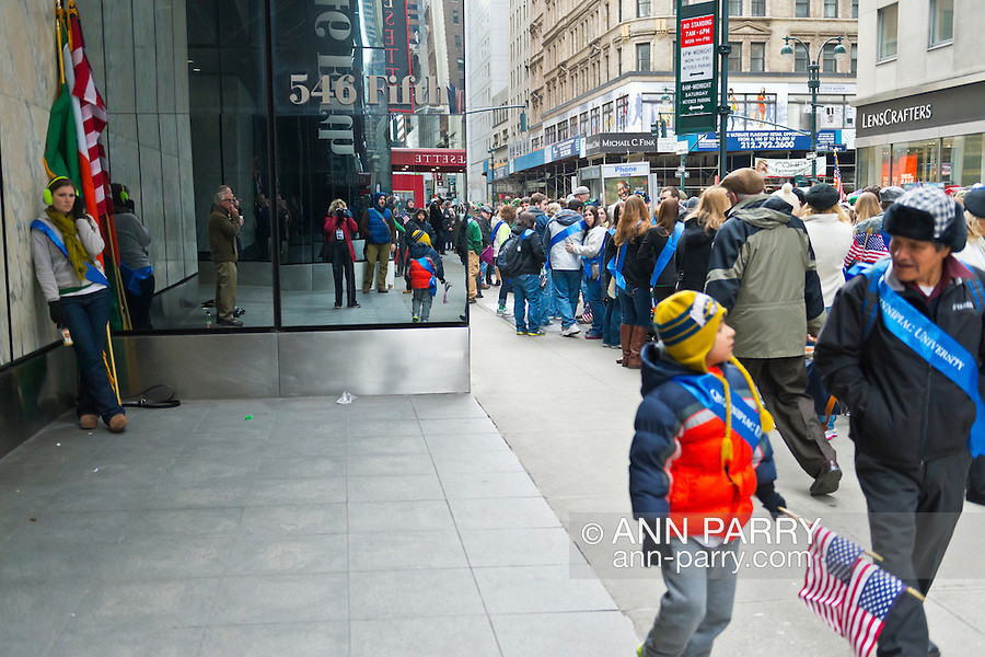 March 16, 2013 - New York, NY, U.S. - On W. 45th Street, with Fifth Avenue in background, people get read to march in the 252nd annual NYC St. Patrick's Day Parade. (Photographer reflected in mirrored side of building.)