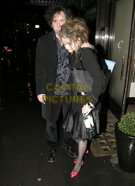 TIM BURTON & HELENA BONHAM CARTER.Pre-BAFTA Party, hosted by Vogue Magazine,  Cecconi, London, February 10th 2005..full length holding bottle drink drunk?.Ref: AH.www.capitalpictures.com.sales@capitalpictures.com.©Capital Pictures.