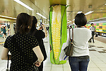 People take a picture of a column displaying a giant corn in the Tokyo Metro passageway in Shinjuku on September 1, 2015, Tokyo, Japan. The Central Union of Agricultural Co-operatives (JA-ZENCHU) is promoting Japanese vegetables with the vegetable columns and a massive 80 meter ''Wall Farmer's Market'' information poster until September 6th. (Photo by Rodrigo Reyes Marin/AFLO)