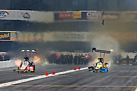 Feb 9, 2014; Pomona, CA, USA; NHRA top fuel dragster driver Sidnei Frigo (right) blows a tire after he explodes an engine alongside Doug Kalitta during the Winternationals at Auto Club Raceway at Pomona. Mandatory Credit: Mark J. Rebilas-